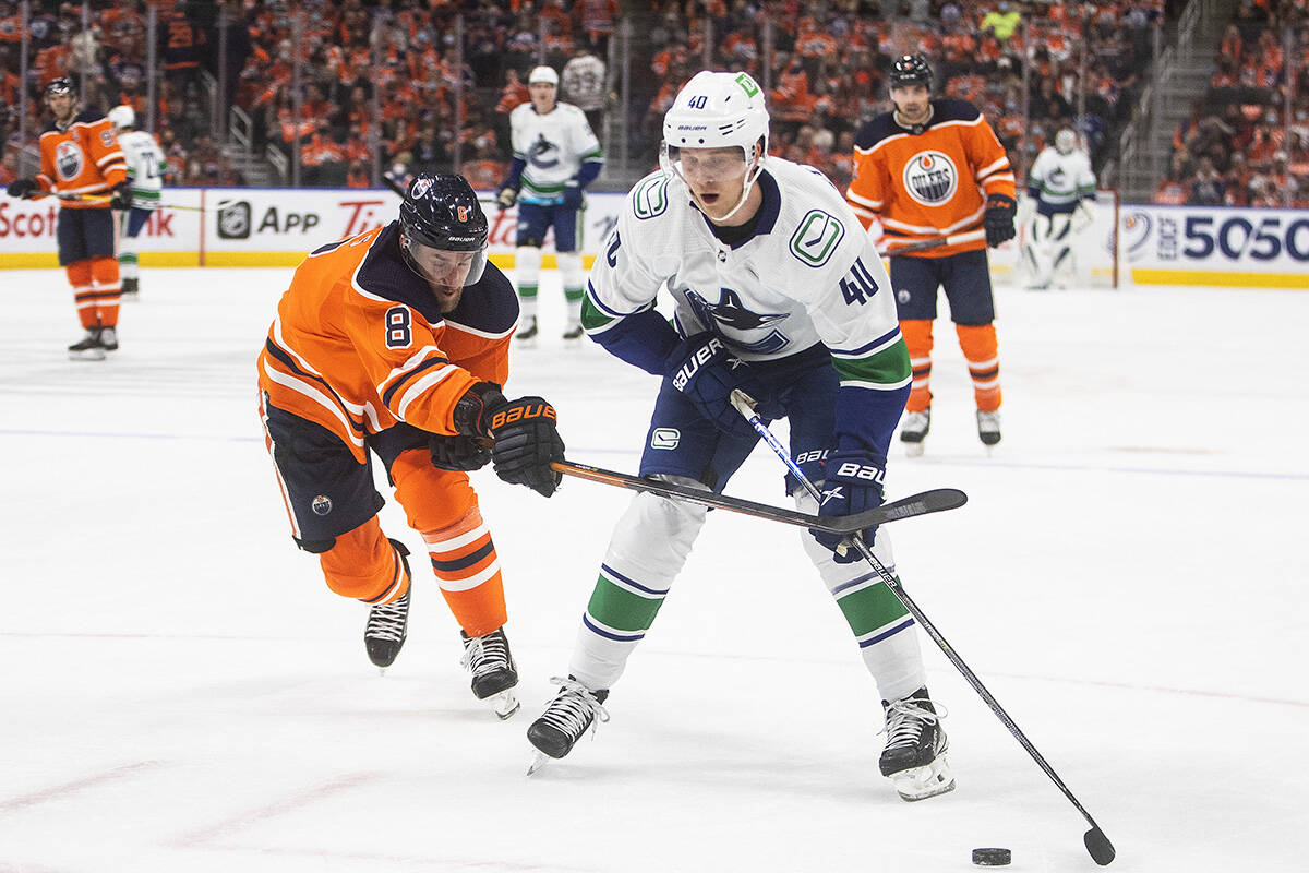 Vancouver Canucks' Elias Pettersson (40) and Edmonton Oilers' Kyle Turris (8) battle for the puck during first period NHL action in Edmonton on Wednesday, October 13, 2021.THE CANADIAN PRESS/Jason Franson
