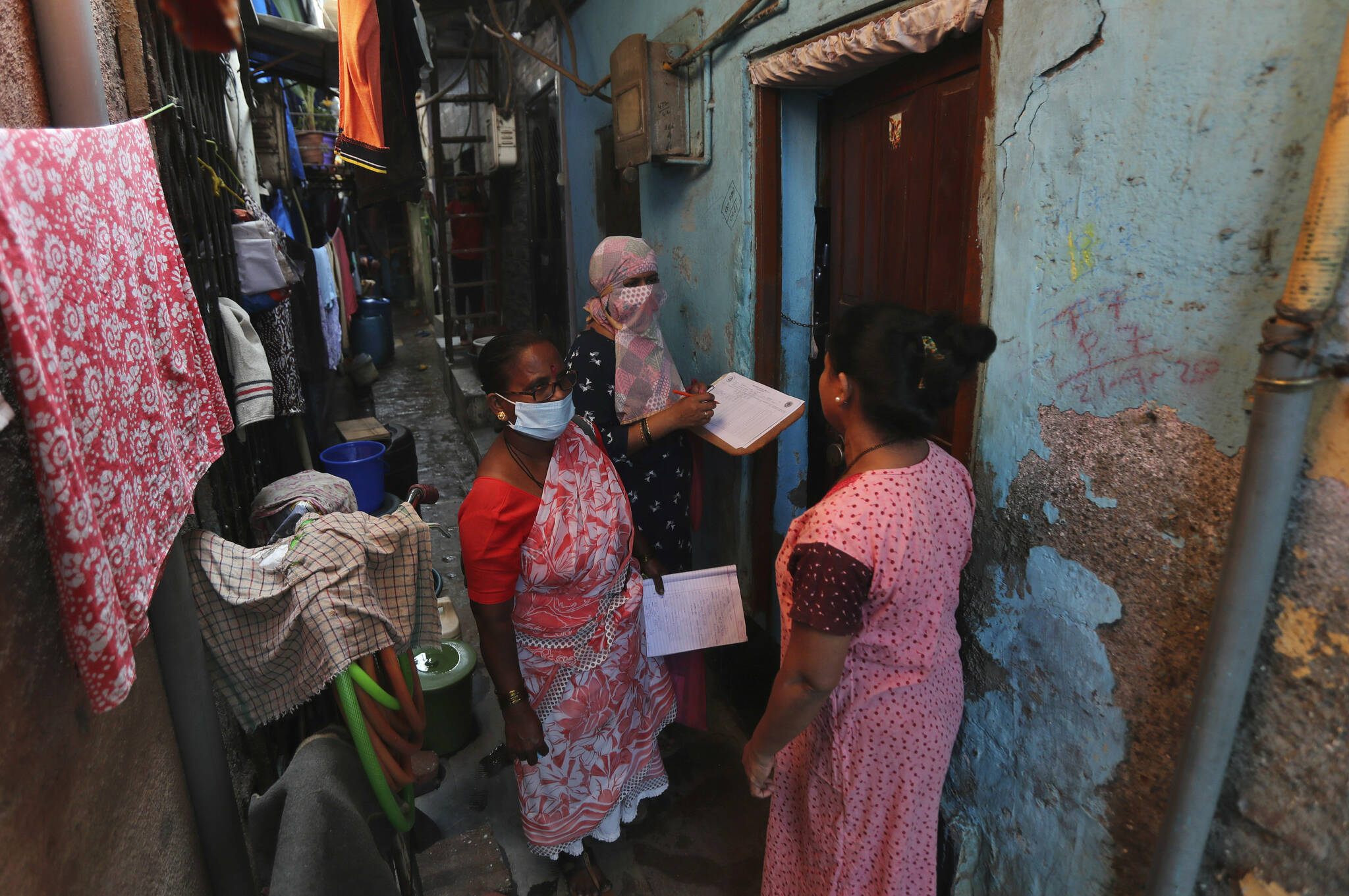 Health workers screen people for tuberculosis and leprosy in Dharavi, one of Asia's biggest slums, in Mumbai, India, Tuesday, Dec. 1, 2020. (AP Photo/Rafiq Maqbool)