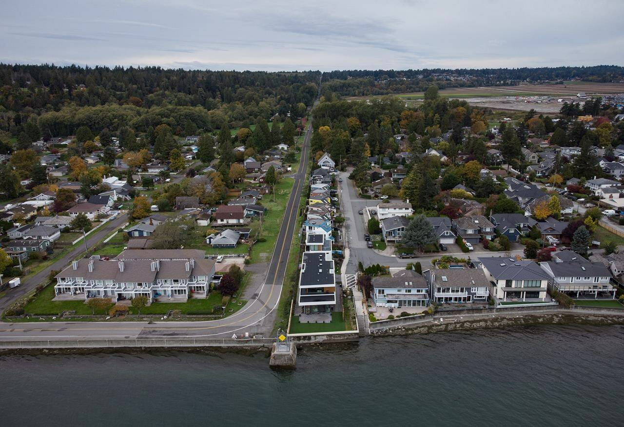 Homes in Delta, B.C., right, and Point Roberts, Wash., left, are separated by the Canada-U.S. border which is just north of Roosevelt Way, centre, in Point Roberts, as seen in an aerial view on Wednesday, October 13, 2021.THE CANADIAN PRESS/Darryl Dyck