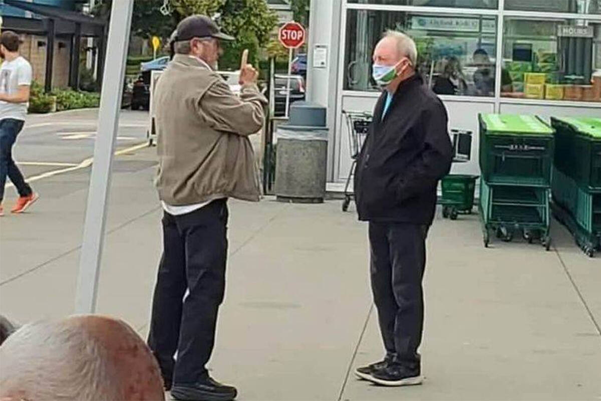 Keep the RCMP in Surrey campaign founder Ivan Scott (left) speaks to Surrey Mayor Doug McCallum in South Surrey Saturday, Sept. 4 after McCallum claimed one of Scott's supporters ran over his foot with their car. (@captainramona Twitter photo)