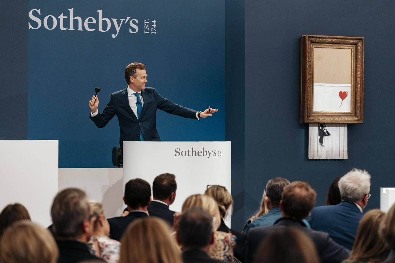 """In this handout photo provided by Sotheby's Auction House, the auction for Banksy's """"Love is the Bin"""" takes place in London, Thursday, Oct. 14, 2021. A work by British street artist Banksy that sensationally self-shredded just after it sold for $1.4 million has sold again for $25.4 million at an auction on Thursday. """"Love is in the Bin"""" was offered by Sotheby's in London, with a presale estimate of $5.5 million to $8.2 million. (Haydon Perrior/Sotheby's Auction House via AP)"""