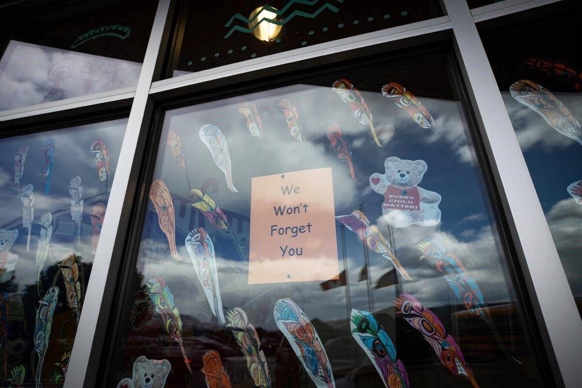 A message is seen on the window of the Sk'elep School of Excellence as the Canadian, Tk'emlups te Secwepemc and B.C. flags are reflected in the window flying at half mast to honour the 215 children whose remains have been discovered buried near the former Kamloops Indian Residential School, in Kamloops, B.C., on Saturday, June 5, 2021. THE CANADIAN PRESS/Darryl Dyck