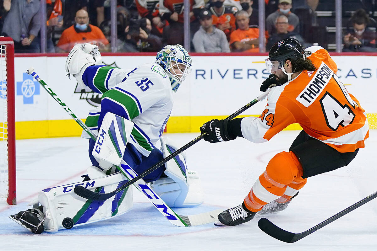 Vancouver Canucks' Thatcher Demko, left, blocks a shot by Philadelphia Flyers' Nate Thompson during the second period of an NHL hockey game, Friday, Oct. 15, 2021, in Philadelphia. (AP Photo/Matt Slocum)