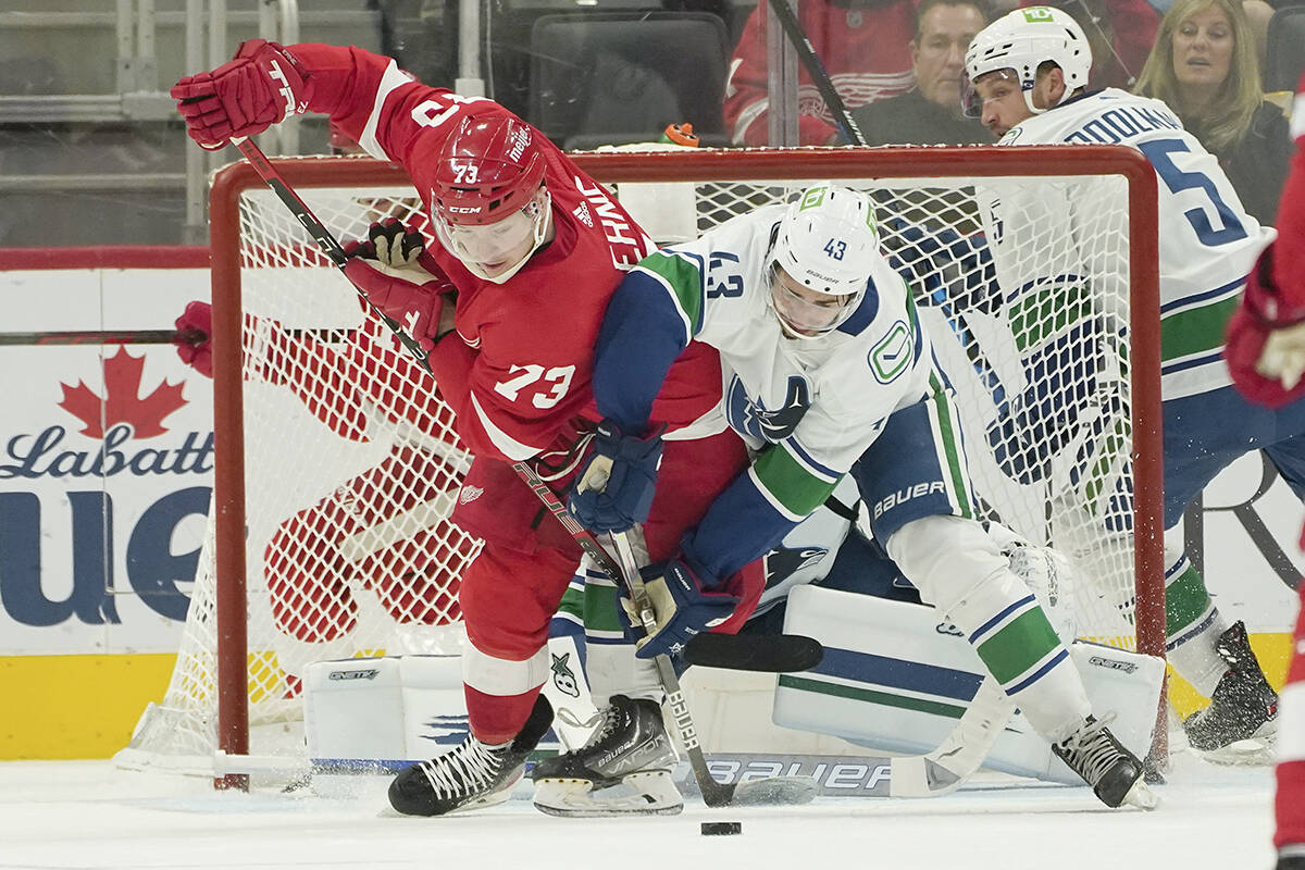 Detroit Red Wings left wing Adam Erne (73) and Vancouver Canucks defenseman Quinn Hughes (43) battle for the puck in the second period of an NHL hockey game Saturday, Oct. 16, 2021, in Detroit. (AP Photo/Paul Sancya) Detroit Red Wings left wing Adam Erne (73) and Vancouver Canucks defenseman Quinn Hughes (43) battle for the puck in the second period of an NHL hockey game Saturday, Oct. 16, 2021, in Detroit. (AP Photo/Paul Sancya)