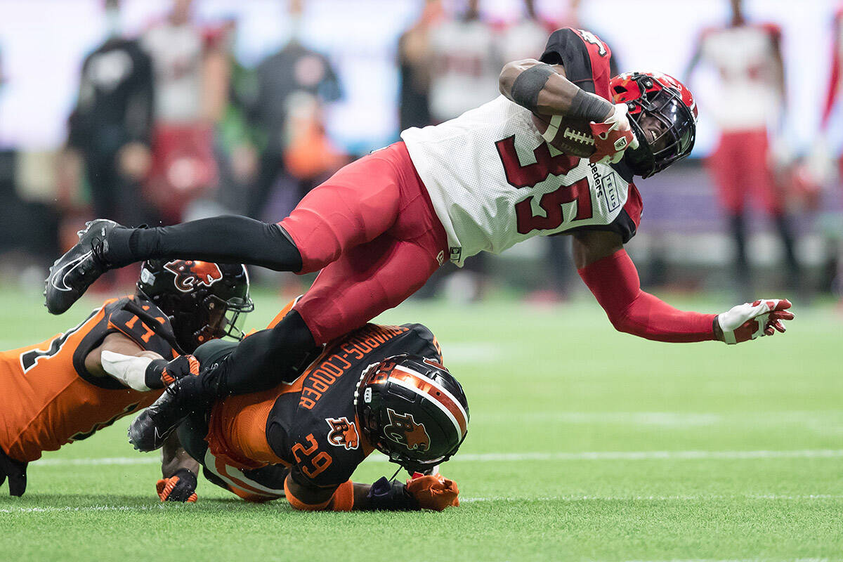Calgary Stampeders' Ka'Deem Carey (35) is upended by B.C. Lions' Jalon Edwards-Cooper (29) as he runs the ball during the second half of a CFL football game in Vancouver, on Saturday, October 16, 2021. THE CANADIAN PRESS/Darryl Dyck