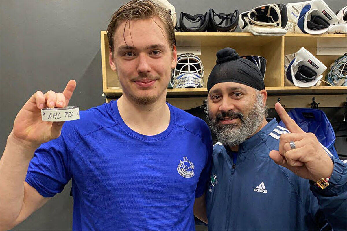 Abbotsford Canucks goalie Arturs Silovs (left) celebrates his first win and Abbotsford's first-ever win with equipment manager Ramandeep 'Chico' Dhanjal on Sunday (Oct. 17). (Abbotsford Canucks Instagram photo)