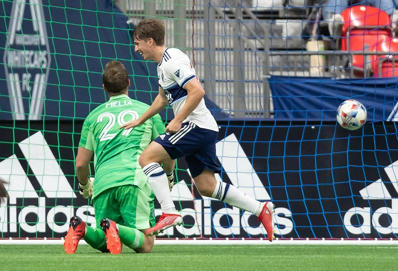 Vancouver Whitecaps' Ryan Gauld, front, celebrates his goal against Sporting Kansas City goalkeeper Tim Melia during first half MLS soccer action in Vancouver, B.C., Sunday, Oct. 17, 2021. THE CANADIAN PRESS/Darryl Dyck