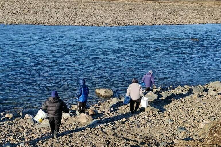 Qajuqturvik Community Food Centre staff members fill water jugs at the Sylvia Grinnell River, just outside Iqaluit, in an undated handout photo. The group has been delivering water to homes and organizations that may not have their own transportation, after the city warned last week its tap water was contaminated with fuel. THE CANADIAN PRESS/HO-Rachel Blais, *MANDATORY CREDIT*