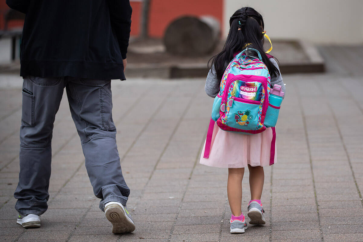 Avalynn Kwok, 4, walks with her dad, Manny Kwok, outside Lynn Valley Elementary School as her parents drop her off for her first day of kindergarten in North Vancouver, B.C., Thursday, Sept. 9, 2021. THE CANADIAN PRESS/Darryl Dyck