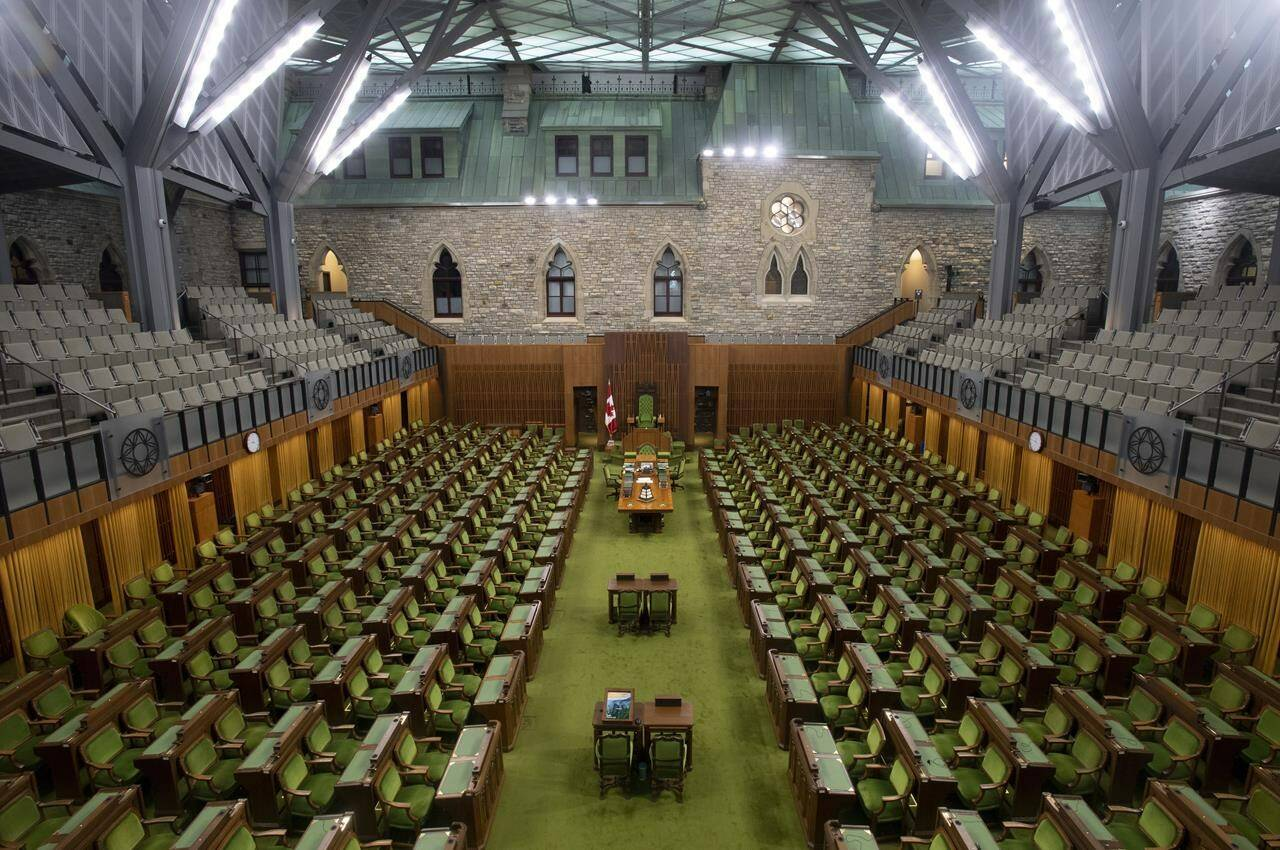The House of Commons chamber is seen empty, Wednesday, April 8, 2020 in Ottawa. When Parliament resumes on Nov. 22, no one will be allowed into the House of Commons precinct unless they are fully vaccinated against COVID-19. THE CANADIAN PRESS/Adrian Wyld