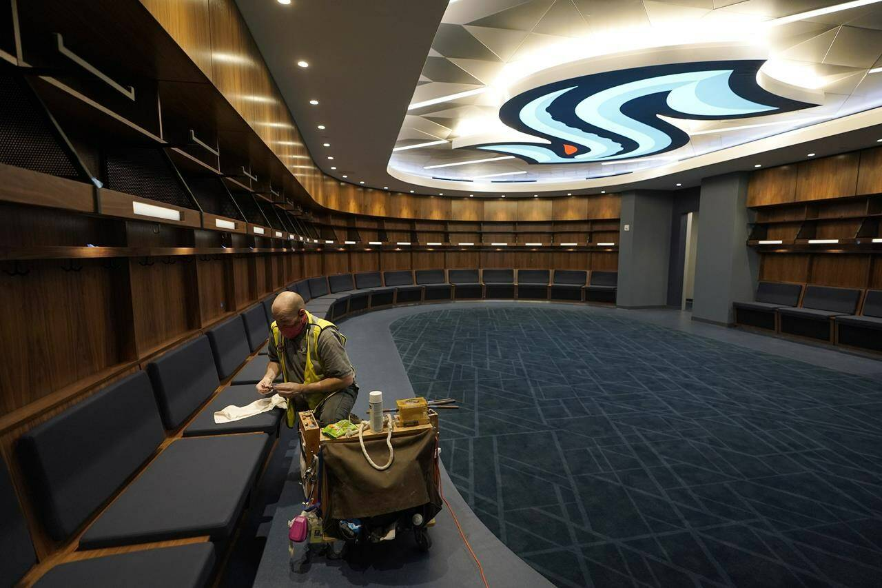 A worker puts the final touches on woodwork in the Seattle Kraken's locker room at Climate Pledge Arena, Wednesday, Oct. 20, 2021, during a media tour ahead of the NHL hockey team's home opener Saturday against the Vancouver Canucks in Seattle. The historic angled roof of the former KeyArena was preserved, but everything else inside the venue, which will also host concerts and be the home of the WNBA Seattle Storm basketball team, is brand new. (AP Photo/Ted S. Warren)