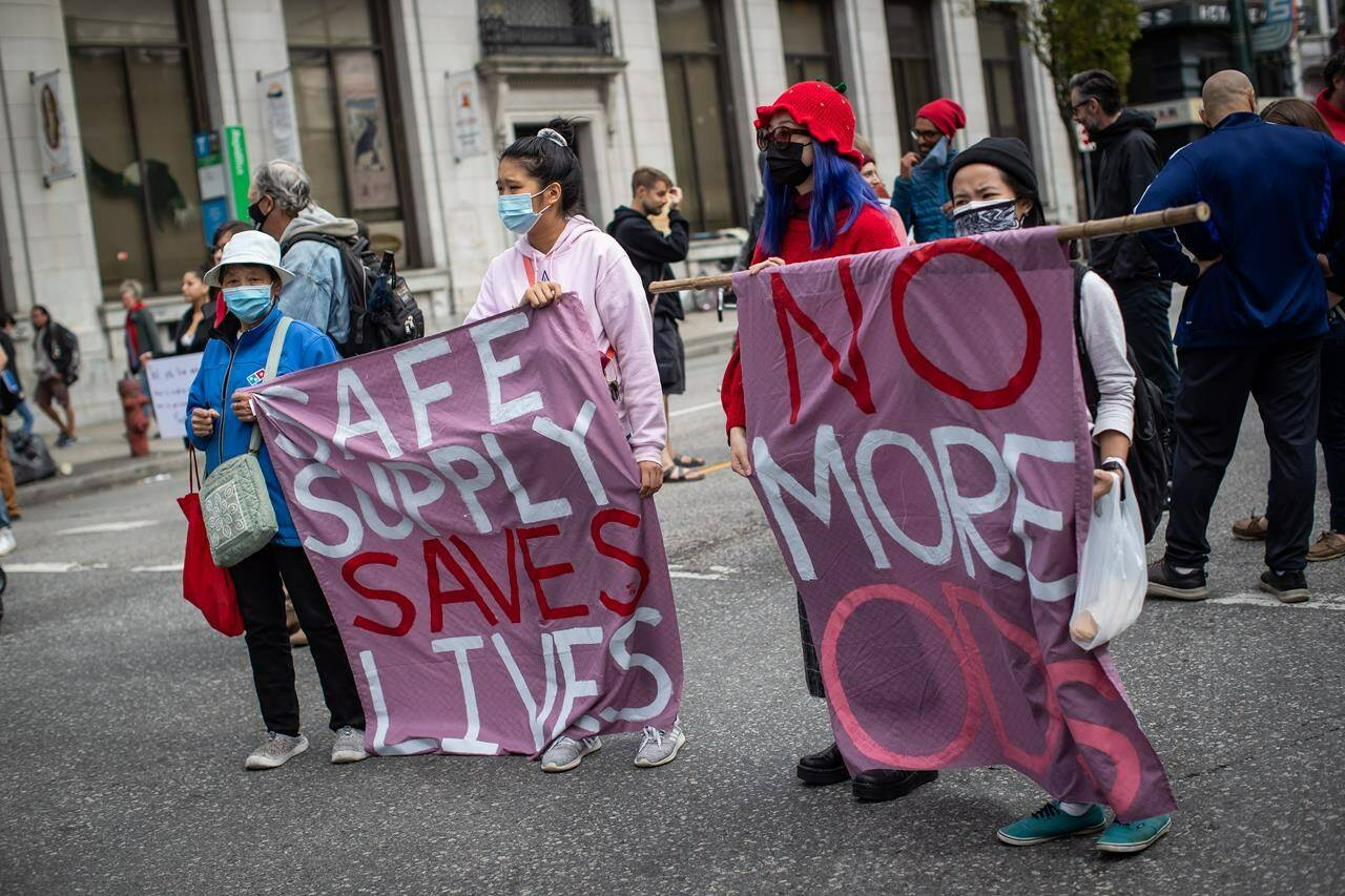 People hold a banner during a march to remember those who died during the overdose crisis and to call for a safe supply of illicit drugs on International Overdose Awareness Day, in Vancouver, on Tuesday, August 31, 2021. Prime Minister Justin Trudeau is being urged to decriminalize the possession and use of illicit drugs as a way to combat the opioid crisis that has resulted in thousands of deaths in Canada.THE CANADIAN PRESS/Darryl Dyck