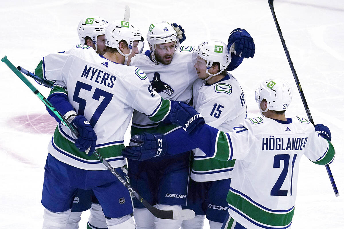Vancouver Canucks centre Jason Dickinson, centre, celebrates with teammates after scoring against the Chicago Blackhawks during the first period of an NHL hockey game in Chicago, Thursday, Oct. 21, 2021. (AP Photo/Nam Y. Huh)