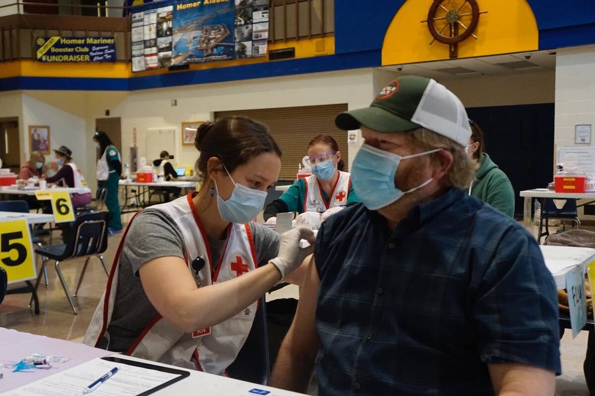 Anna Lewald, left, a registered nurse at South Peninsula Hospital, gives Dave Aplin, right, an influenza vaccine at a flu and Pfizer COVID-19 vaccine clinic Friday, Oct. 15, 2021, at Homer High School in Homer, Alaska. (Photo by Michael Armstrong/Homer News)