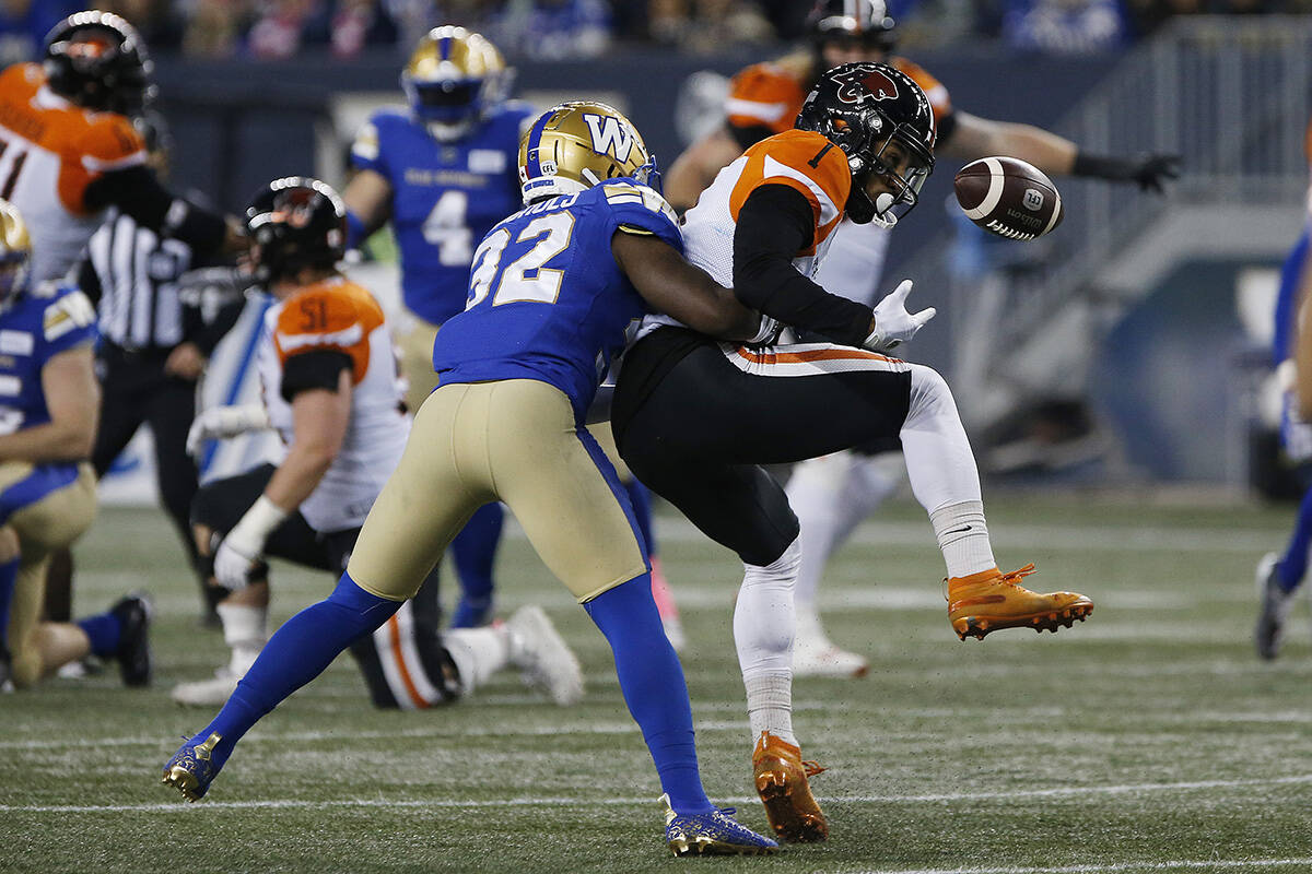 Winnipeg Blue Bombers' Deatrick Nichols (32) knocks the ball away from B.C. Lions' Lemar Durant (1) as he attempts the catch during the first half of CFL action in Winnipeg Saturday, October 23, 2021. THE CANADIAN PRESS/John Woods