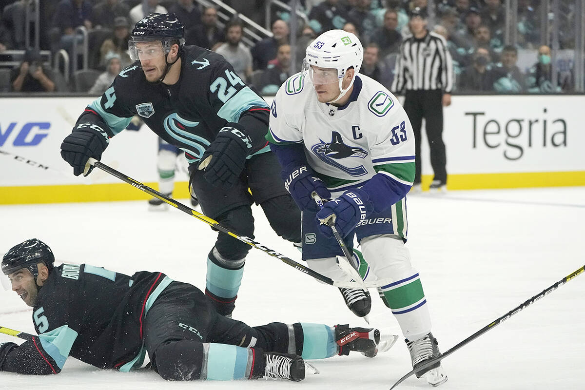 Vancouver Canucks centre Bo Horvat (53) watches his goal hit the net, next to Seattle Kraken defencemen Jamie Oleksiak (24) and Mark Giordano (5) during the second period of an NHL hockey game Saturday, Oct. 23, 2021, in Seattle. (AP Photo/Ted S. Warren)