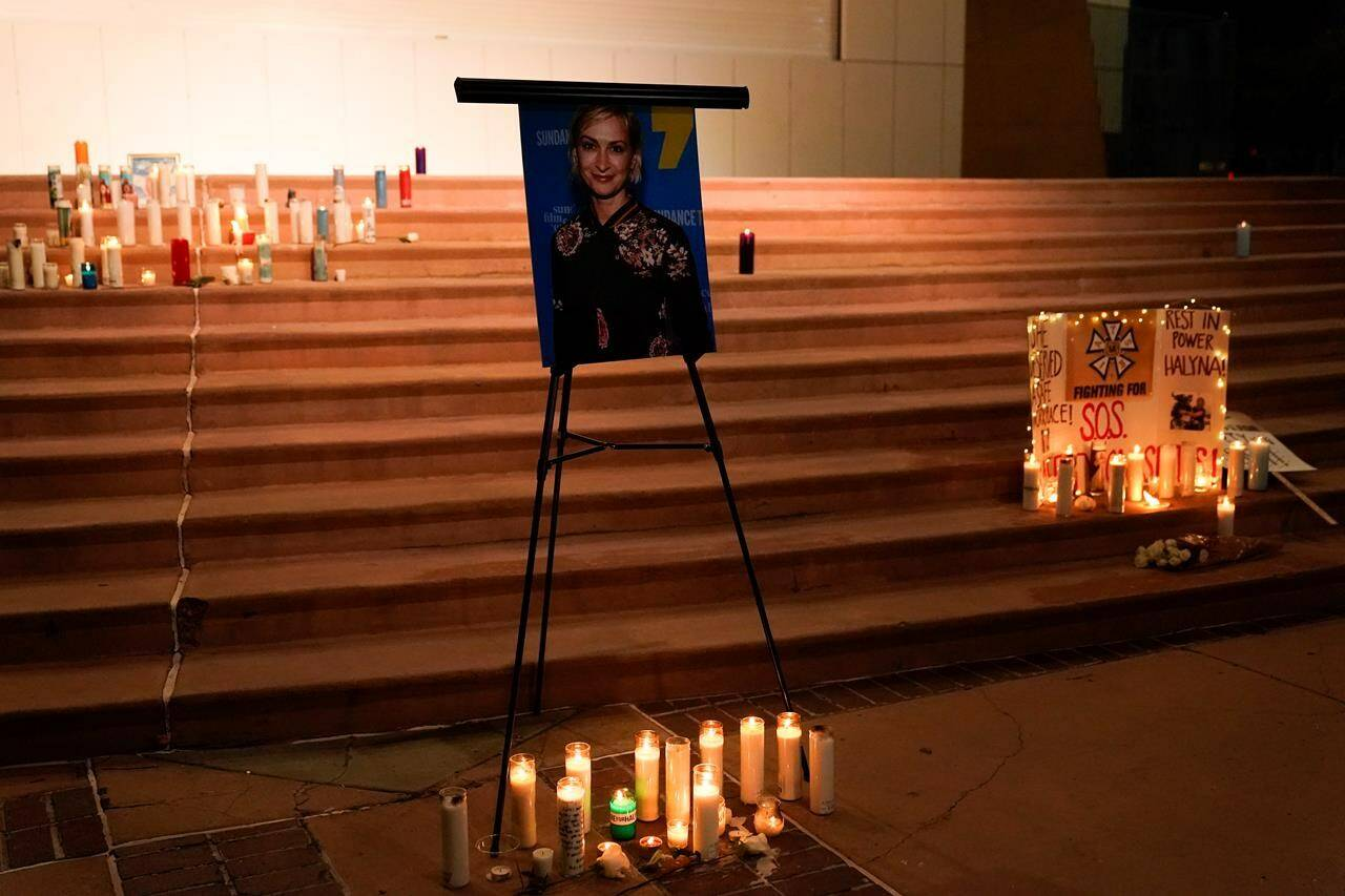 Candles are lit around a photo of cinematographer Halyna Hutchins during a candlelight vigil in Albuquerque, N.M., Saturday, Oct. 23, 2021. Hutchins died on Thursday after she was fatally shot by actor Alec Baldwin with a prop gun on a New Mexico film set. THE CANADIAN PRESS/AP, Jae C. Hong