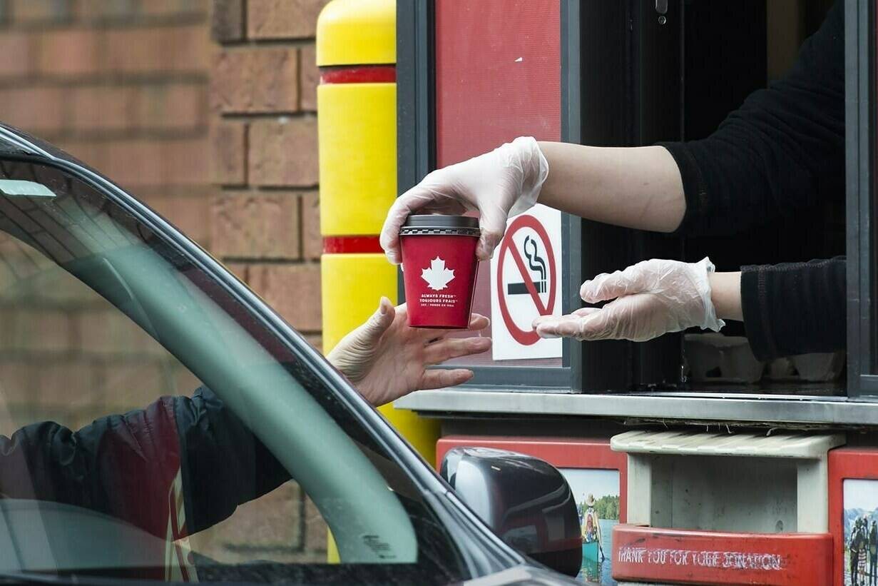 A Tim Hortons employee hands over a coffee from a drive-through window to a customer in Mississauga, Ont., on Tuesday, March 17, 2020. THE CANADIAN PRESS/Nathan Denette