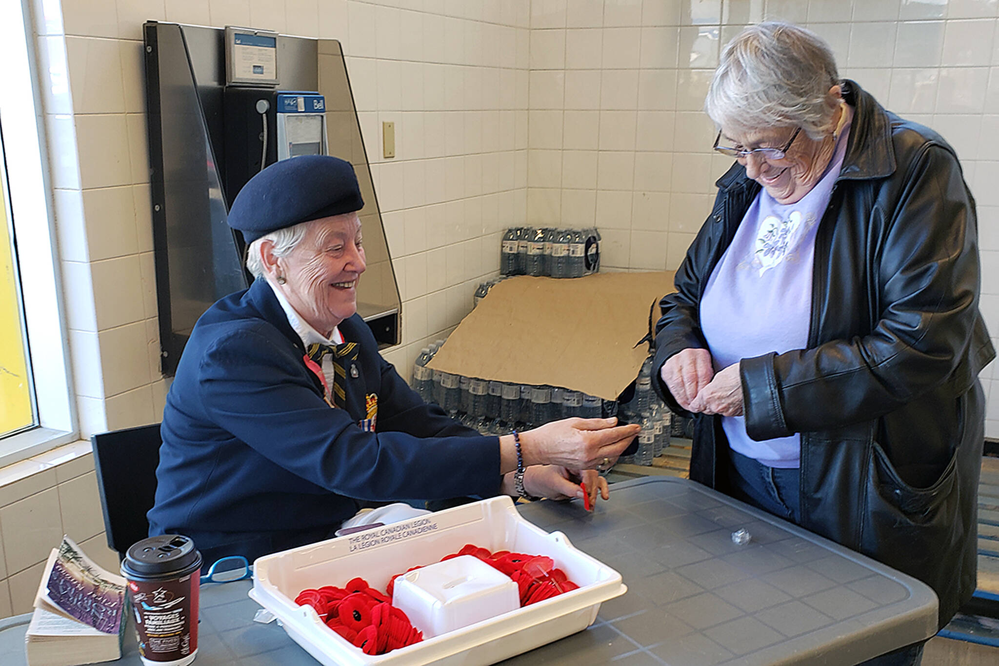 Poppy Drive: Royal Canadian Legion member Marlene Ferguson helps Peggy Lucas with her poppy at the No Frills grocery story in Ponoka Oct. 25, the first day of the annual poppy campaign. Legion members will be at local stores and other venues until Nov. 10 selling poppies. Photo by Jordie Dwyer