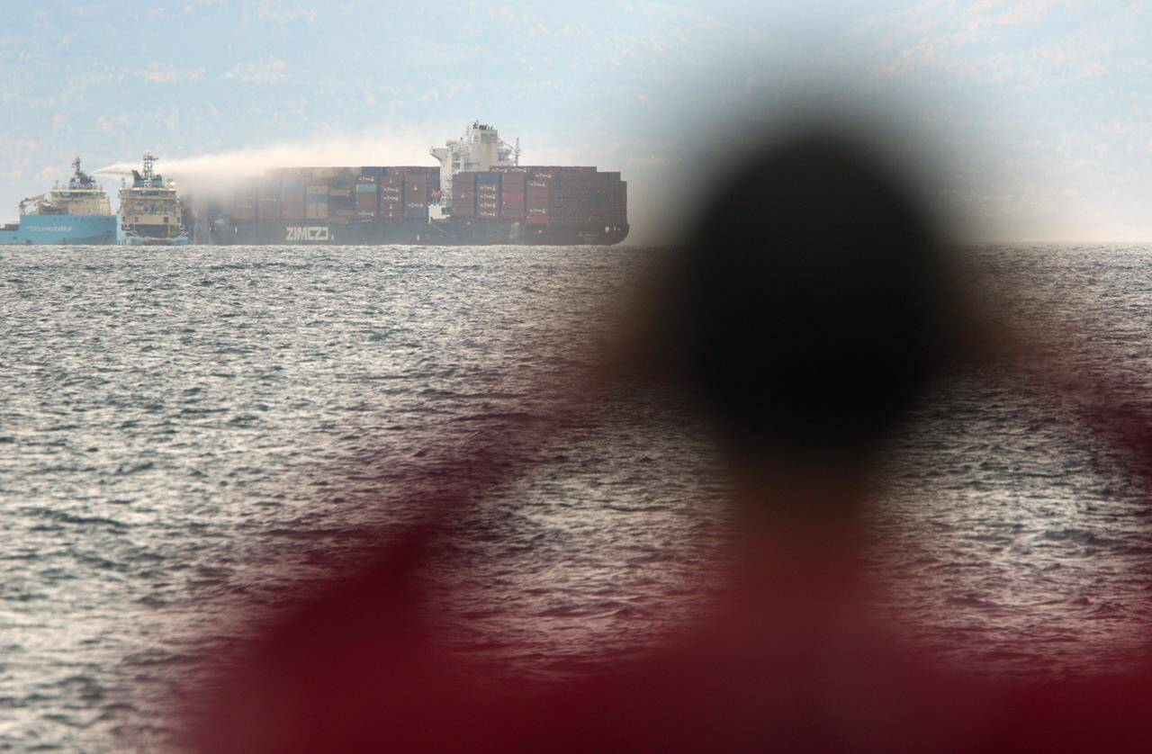Ships work to control a fire aboard the MV Zim Kingston about eight kilometres from the shore in Victoria, B.C., on Sunday, Oct. 24, 2021. The container ship caught fire Friday and 16 crew members were evacuated and brought to Ogden Point Pier. THE CANADIAN PRESS/Chad Hipolito