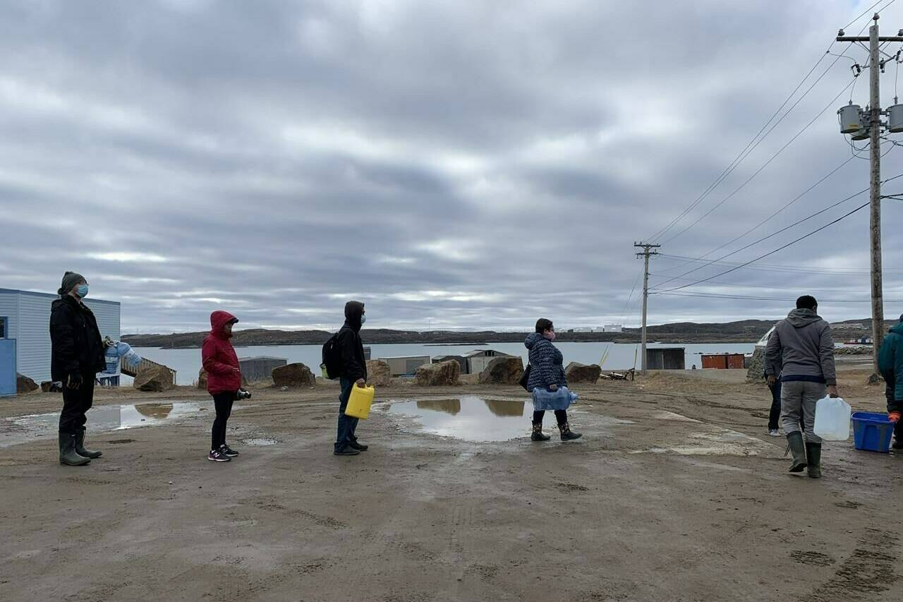 Residents line up to fill containers with potable water in Iqaluit, Nunavut on Thursday, Oct. 14, 2021. The City of Iqaluit says an old underground spill is likely responsible for fuel that is contaminating the city's tap water. THE CANADIAN PRESS/Emma Tranter