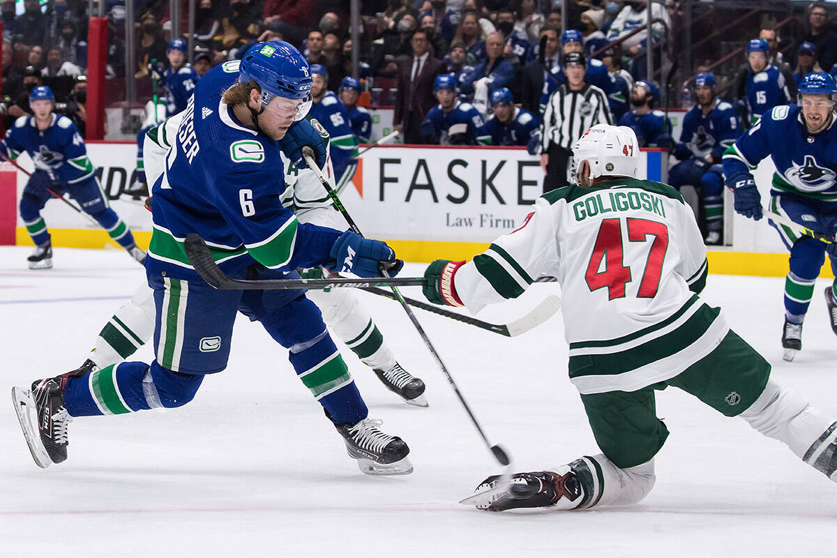 Vancouver Canucks' Brock Boeser (6) takes a shot on goal as Minnesota Wild's Alex Goligoski (47) defends during the second period of an NHL hockey game in Vancouver, on Tuesday, October 26, 2021. THE CANADIAN PRESS/Darryl Dyck